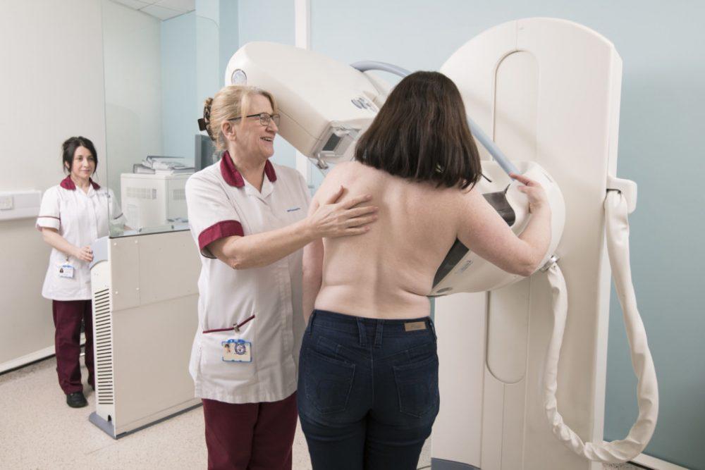 Female nurse assisting a female patient undergoing mammogram breast screening